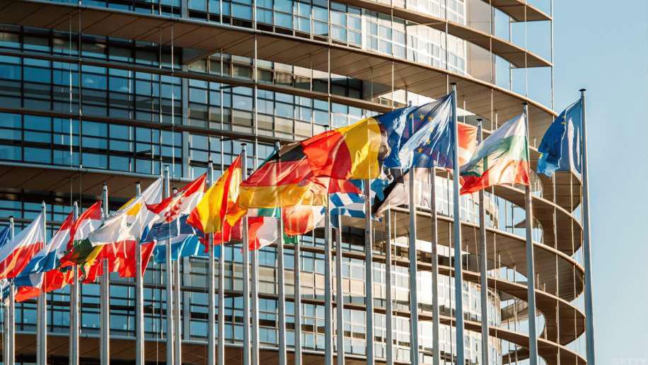 Medlemsländernas flaggor framför EU-parlamentet.